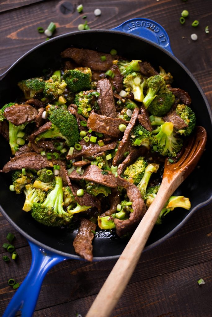 Overhead view of a healthy sauteed beef and broccoli flowerets meal in a cast iron pan, with a wooden serving spoon resting on the pan.