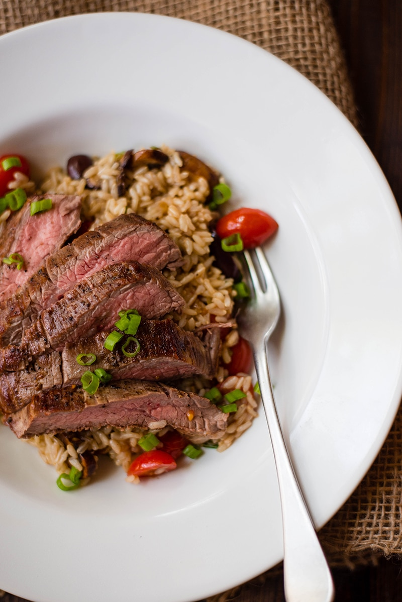Overhead image of a white bowl containing Brown Rice Pilaf with Flank Steak, with a fork resting on the side of the bowl.