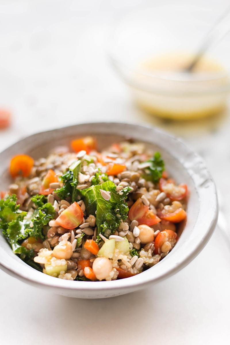 Close up view of a quinoa lentil salad in a white bowl, and behind the bowl is a small glass bowl of lemon vinaigrette.