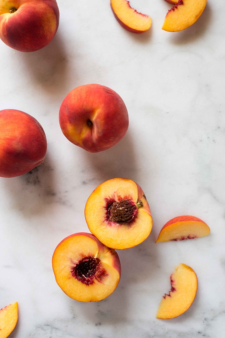 Fresh peaches, sliced and whole, ready to be diced and added to the peach muffins recipe