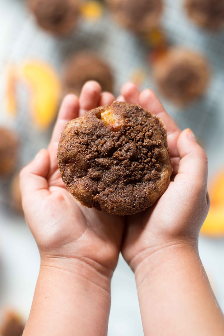 Young child's hands holding a freshly baked peach muffin