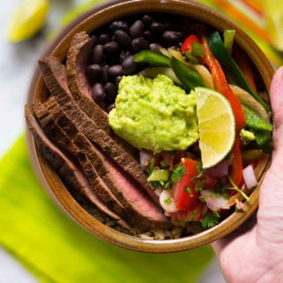 Hand holding the steak fajita bowl with cilantro lime rice, ready to eat.