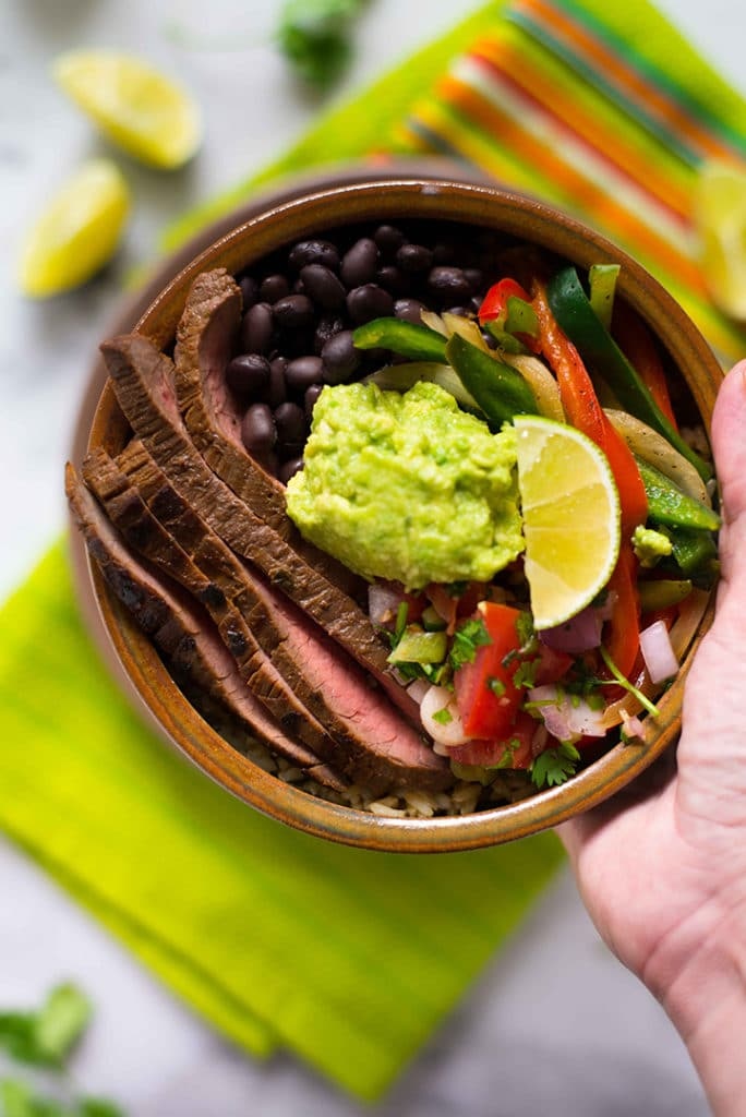 Hand holding the steak fajita bowl with cilantro lime rice topped with avocado, ready to eat.