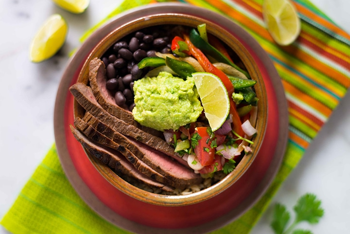 Close up shot of the steak fajita bowl with cilantro lime rice, topped with guacamole and a lime wedge, ready to eat.