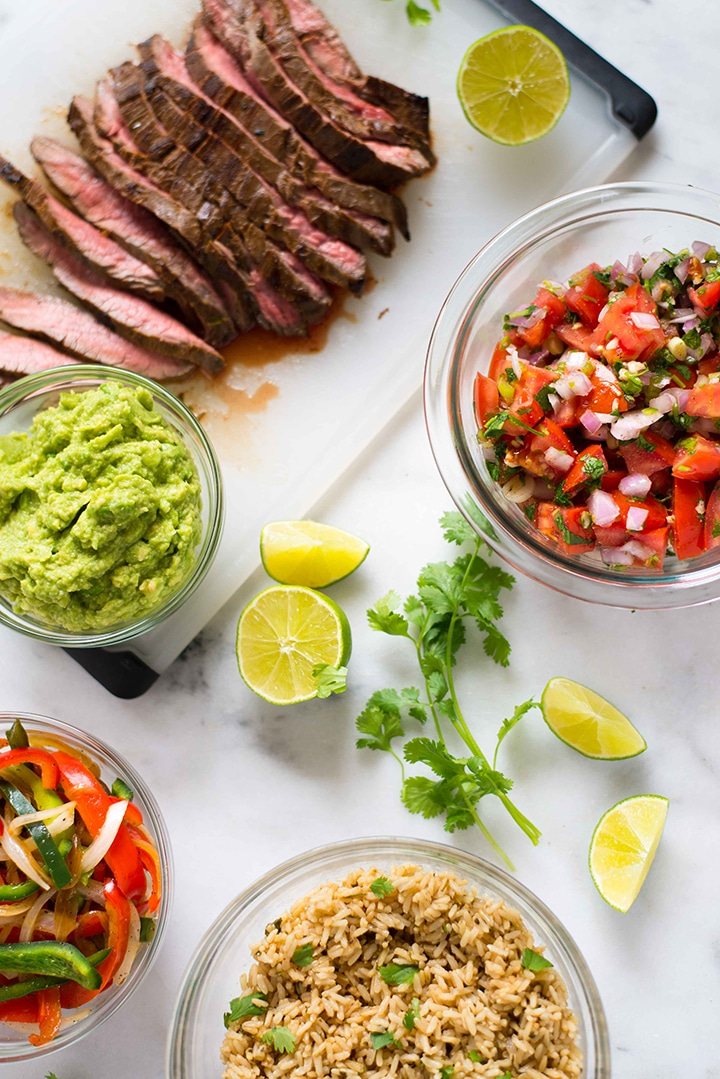 Overhead image of the various toppings for the steak fajita bowl, including the sliced marinated flank steak, cilantro lime rice, pico de gallo, guacamole, fajita bell peppers and onions, and lime wedges.