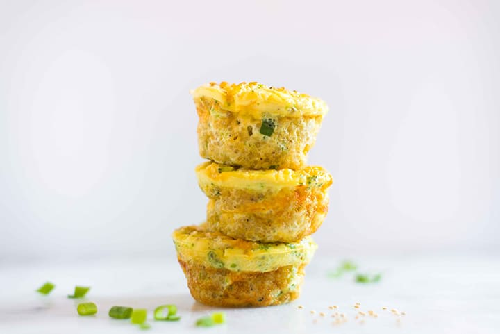 Three baked egg muffin cups, stacked on top of eachother, ready to enjoy for a quick egg muffin cup on the go breakfast.
