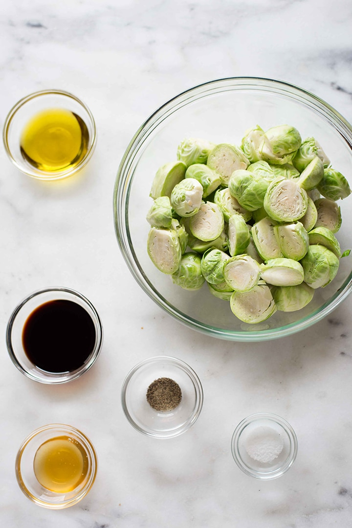 Six ingredients separated before mixing together for the roasted brussels sprouts, including raw honey, raw and halved brussels sprouts, olive oil, balsamic vinegar, sea salt, and pepper.