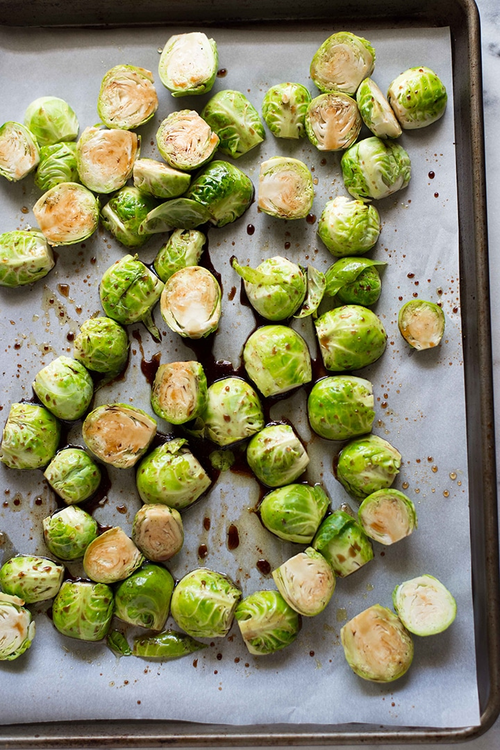 The brussels sprouts have been coated with balsamic honey mixture and are on a parchment sheet, ready to be roasted in the oven.