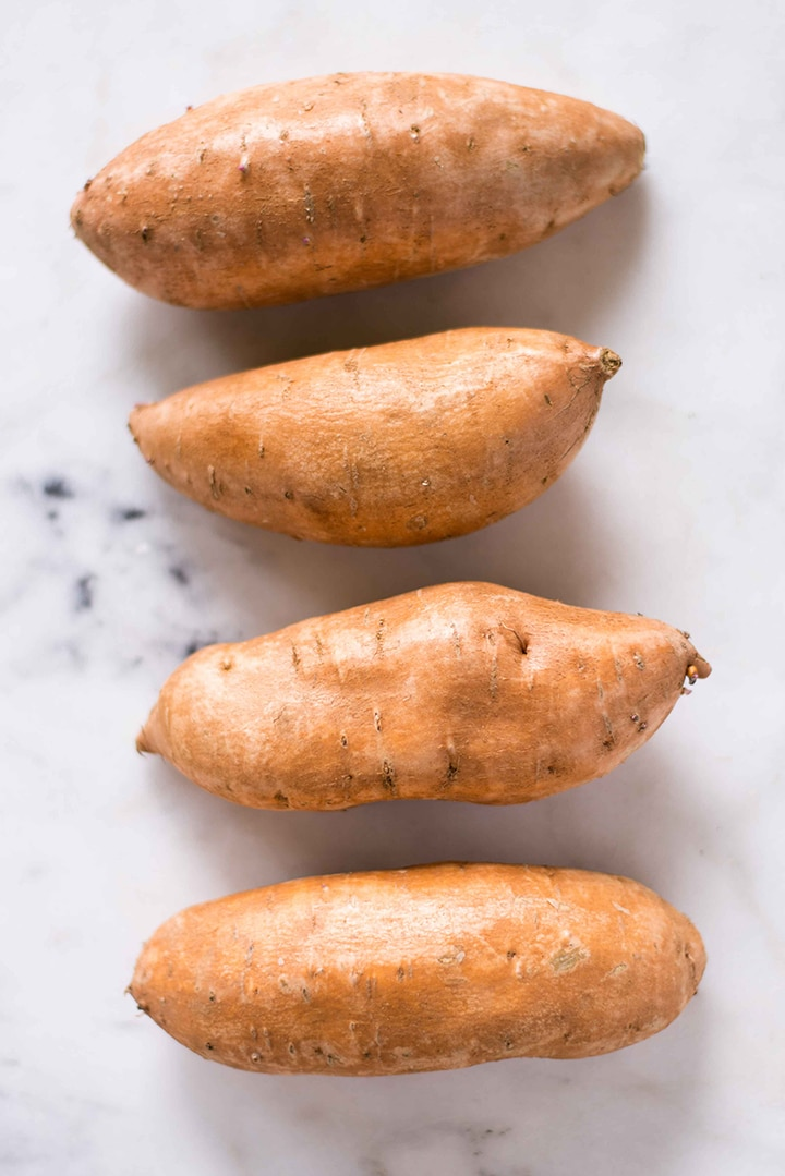 Four uncooked sweet potatoes laying on a marble counter in a row, ready to be baked to make the sweet potato tots.
