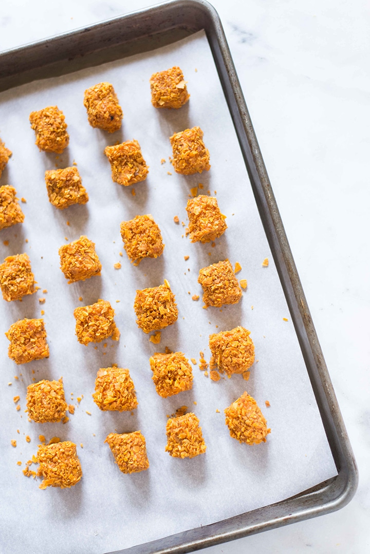 Sweet potato tots, uncooked, and on the rimmed baking sheet, ready to be placed in the oven.