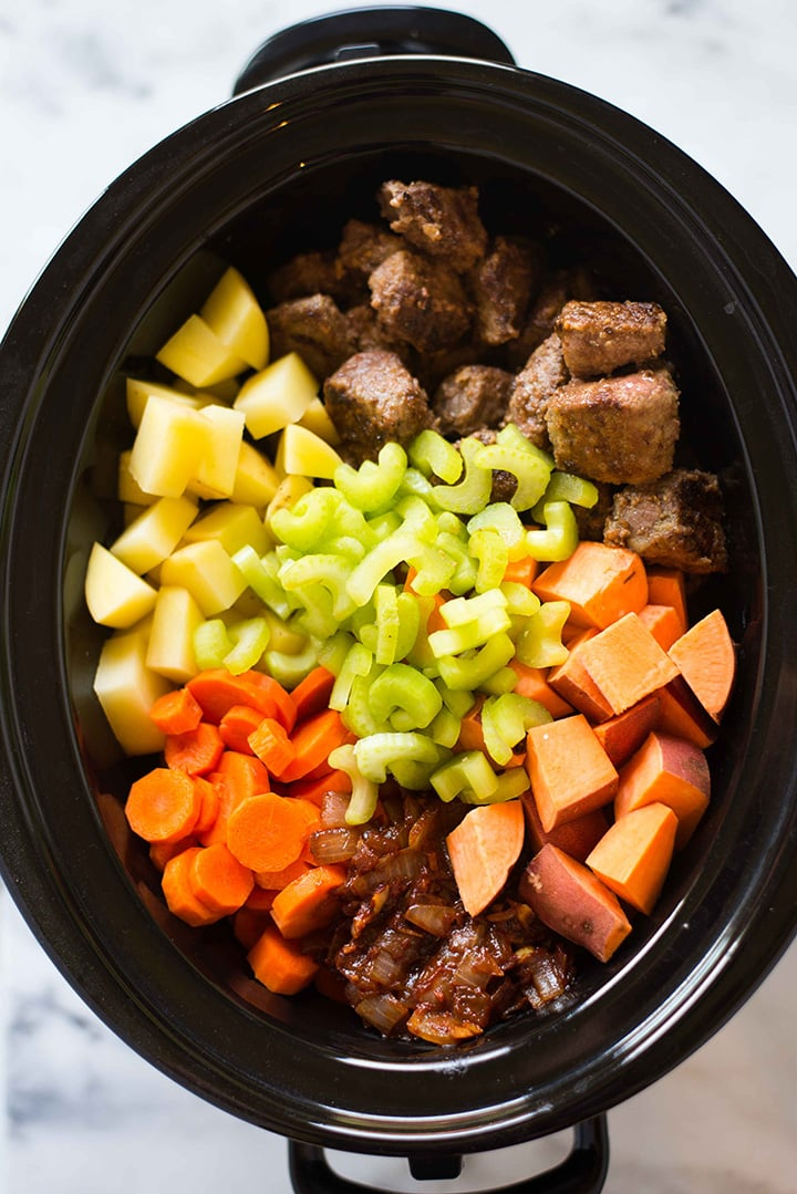 Bowl of slow cooker filled with uncooked sweet potatoes, cubed yukon potatoes, sliced celery, seared beef, and spices, ready to be mixed and cooked to make the slow cooker beef stew.