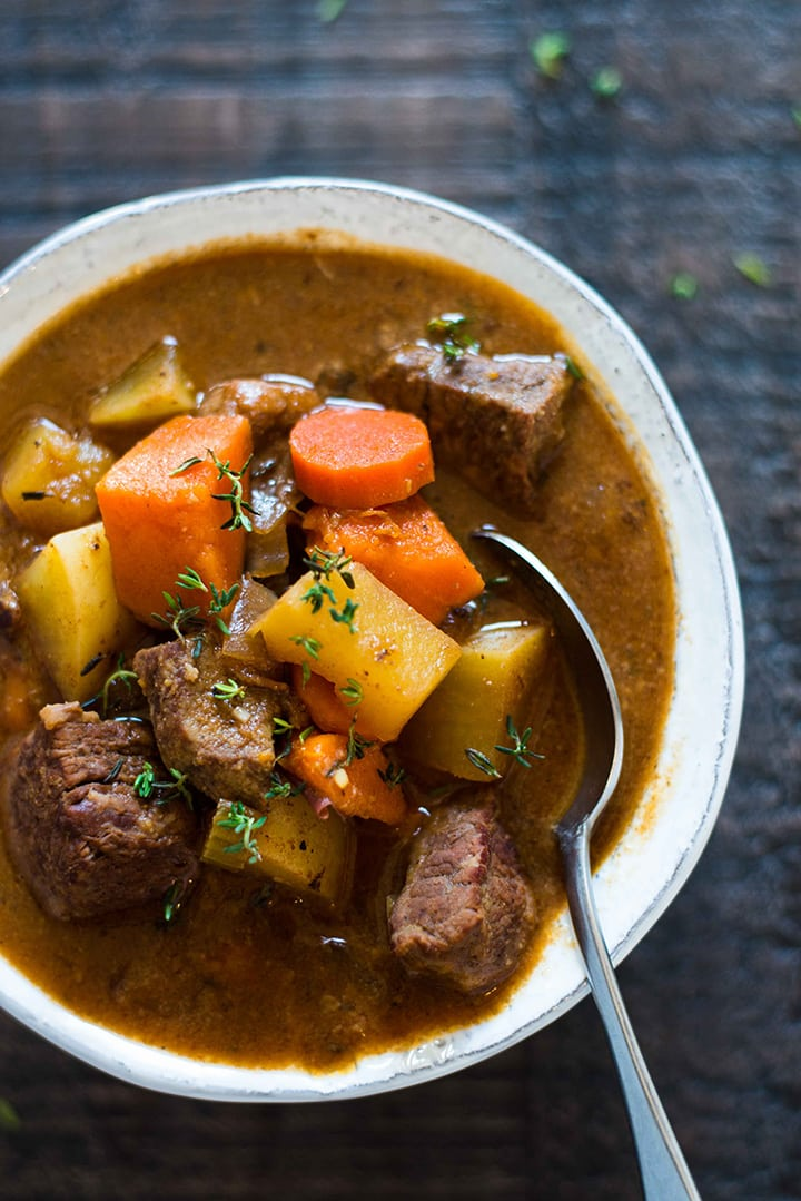 Bowl of slow cooker beef stew, filled with cooked yukon potatoes, sliced carrots, beef chunks, and sweet potatoes, with a spoon in it and ready to eat.
