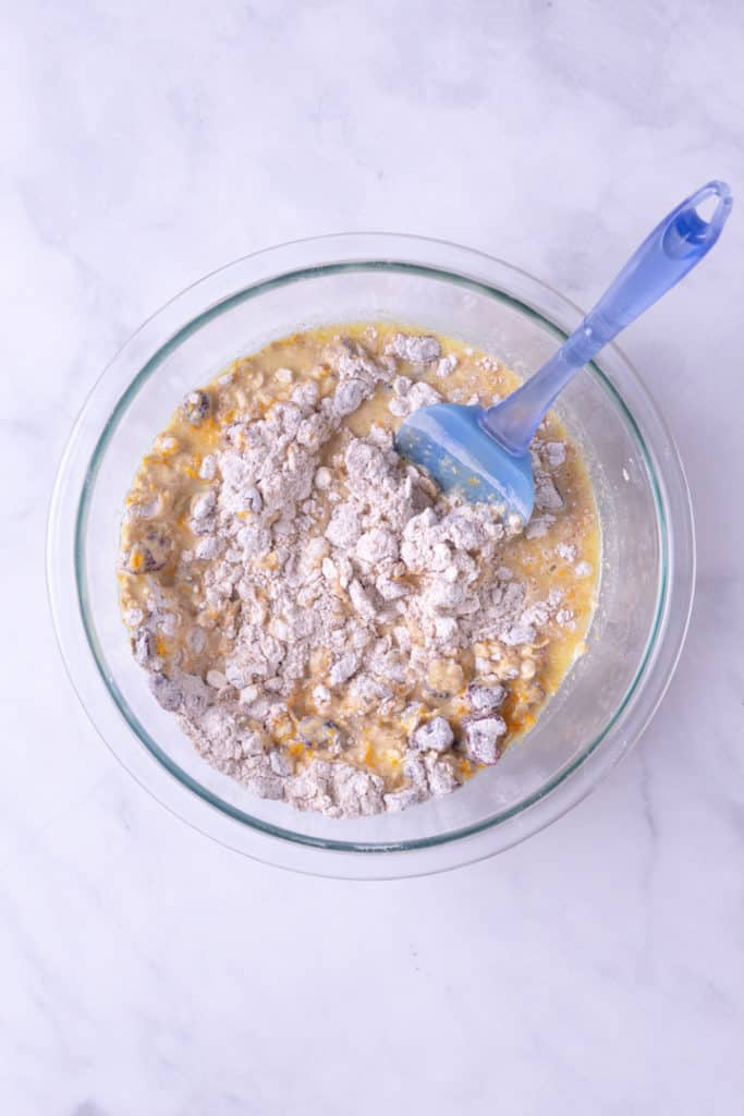 Overhead image of a glass bowl containing the mixture of wet and dry ingredients for Cranberry Orange Bread, partially mixed and a blue spatula is in the bowl also.