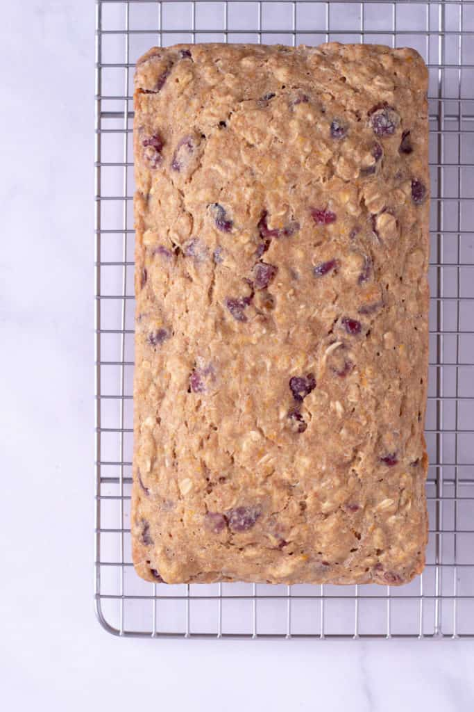 Overhead view of a baked Cranberry Orange Bread, cooling on a metal rack.