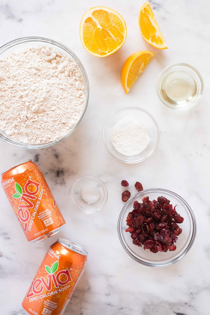 Ingredients required for the cranberry orange bread, including orange Zevia soda, whole wheat pastry flour, sea salt, dried unsweetened cranberries, and baking powder.