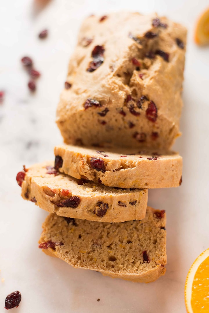 Loaf of cranberry orange bread has been sliced and it is clear that the cranberries are throughout the bread and that it is moist.