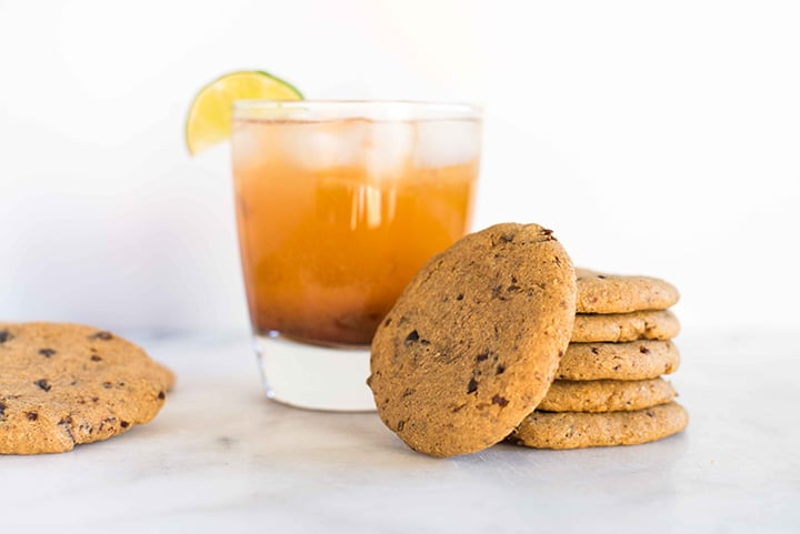 Non alcoholic dark and stormy mocktail sitting next to a pile of freshly baked ginger cookies.