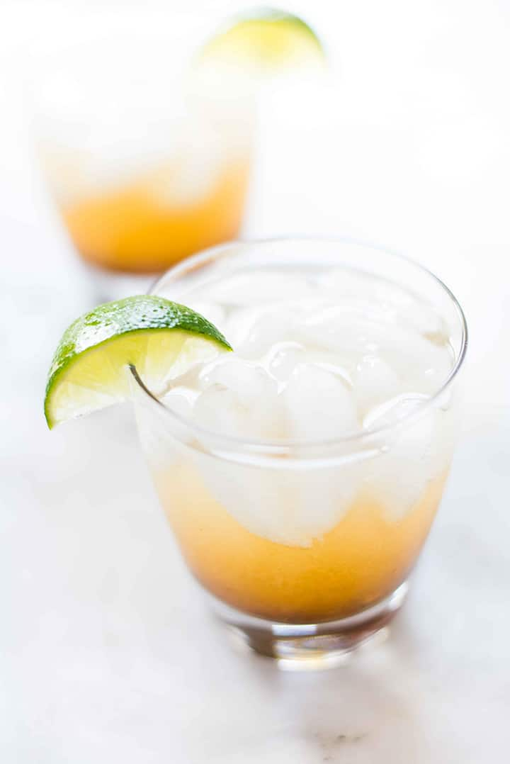 Two glasses of non alcoholic dark and stormy using just three ingredients and no added sugars. The glasses of dark and stormy have fulled with ice and have a lime wedge on the rim.