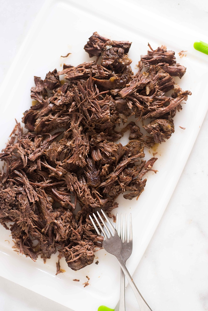 Shredded barbacoa beef that has been cooked until tender in the Instant Pot and is ready to be made into barbacoa tacos.