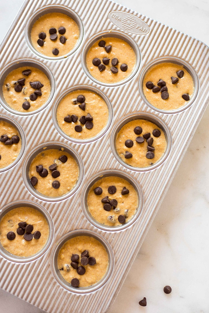 Muffin tin filled 3/4 way full with the pumpkin chocolate chip muffin batter and then topped off with additional dark chocolate chips before being placed in the oven.