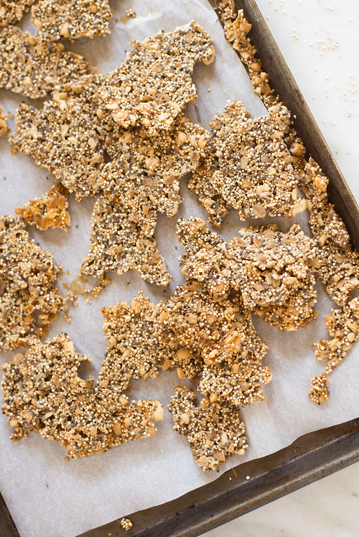 Rimmed baking sheet with the broken up pieces of the quinoa peanut brittle, which have been baked until solid. and then broken up using your hands.
