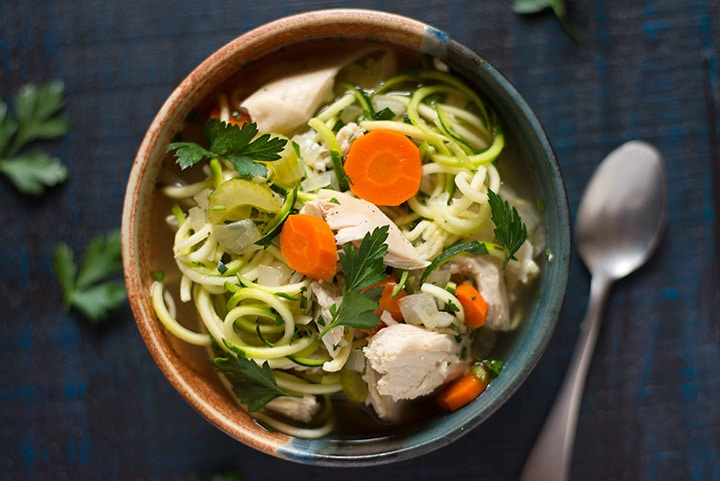 Horizontal image of a bowl of slow cooker chicken noodle soup, ready to be eaten.