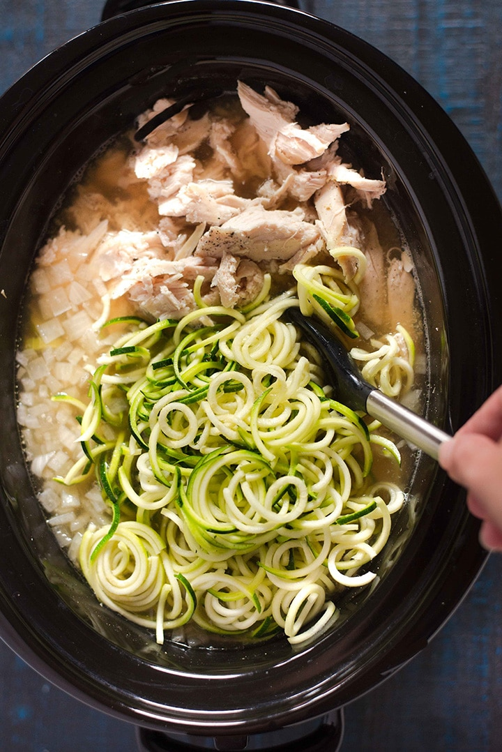 Adding the spiralized zucchini noodles to the slow cooker to allow them to cook, showing how the chicken has now been fully cooked and the vegetables are tender.