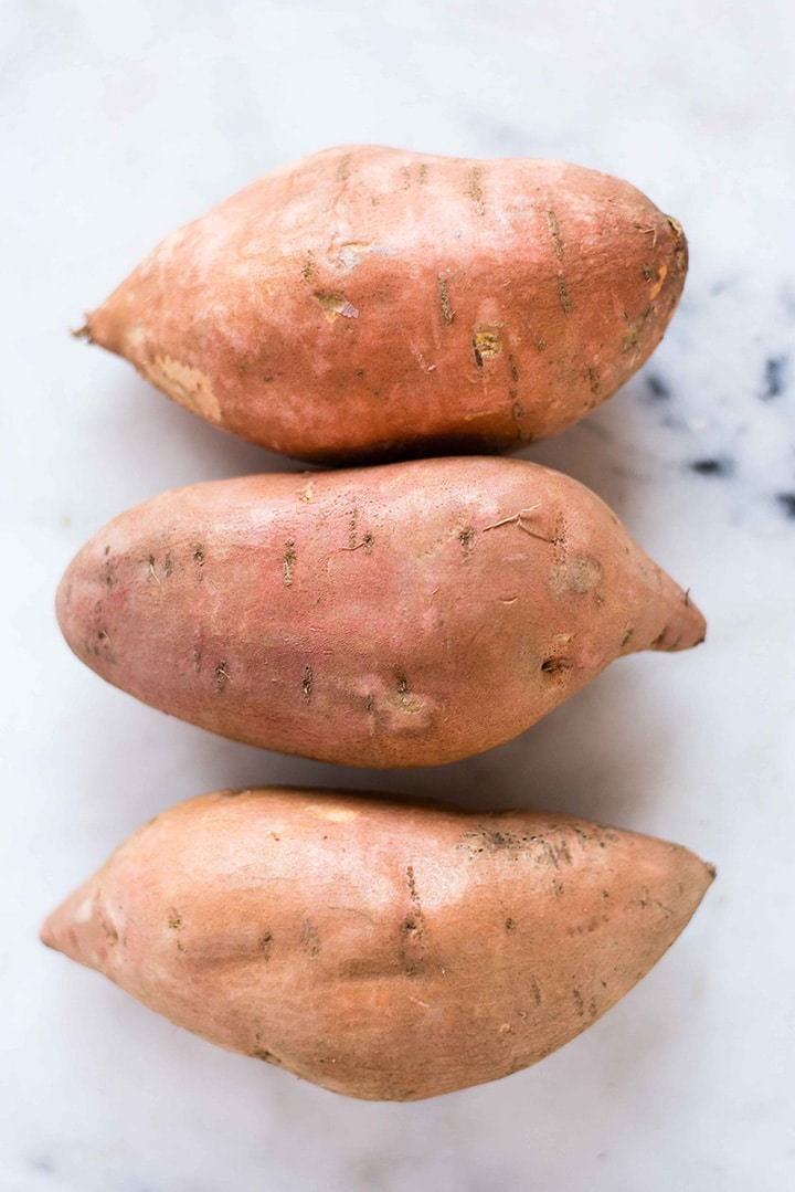 Three raw sweet potatoes laying in a row, ready to be baked and used in the Sweet Potato Hummus recipe.