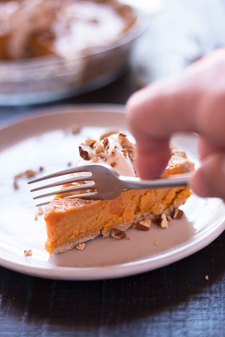 Side view of a slice of the southern sweet potato pie with a hand with a fork taking a bite.