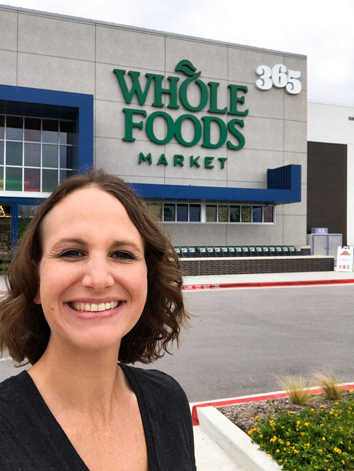 Image of Lacey Baier standing outside a Whole Foods Market 365 in Cedar Park about to complete the $100 challenge of making a full Thanksgiving Dinner Menu.