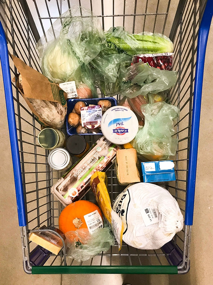 Overhead view of a Whole Foods 365 grocery cart filled with groceries to make a full Thanksgiving Dinner Menu. Grocery cart includes produce, meats, dairy, and more.