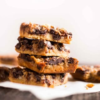 Easy paleo 7 layer bars that are layered with coconut flakes, dark chocolate, almond meal crust, salted caramel sauce, and paleo coconut condensed milk! | A Sweet Pea Chef