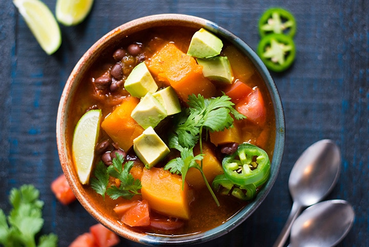 Bowl of butternut squash instant pot chili, where you can see the cooked, diced butternut squash, cooked black beans, tomatoes, and it is topped with fresh avocado, lime wedge, jalapeno, and cilantro.