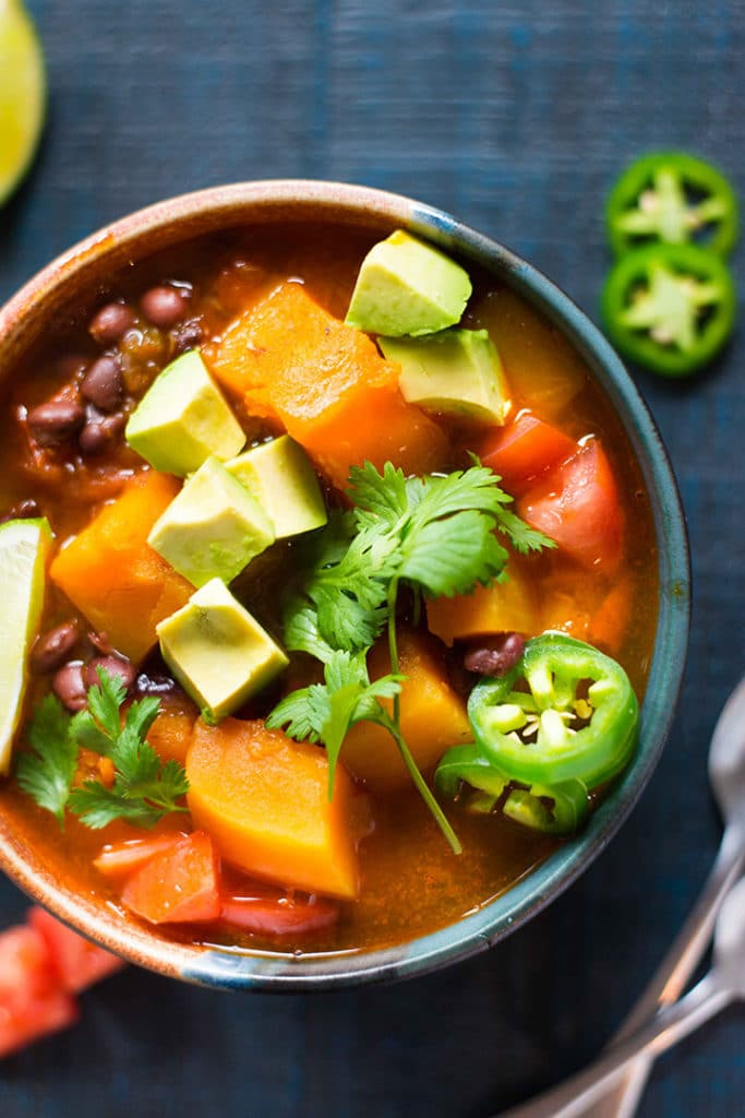Bowl of butternut squash instant pot chili from overhead, which is topped with fresh cilantro and sliced jalapeno pepper.