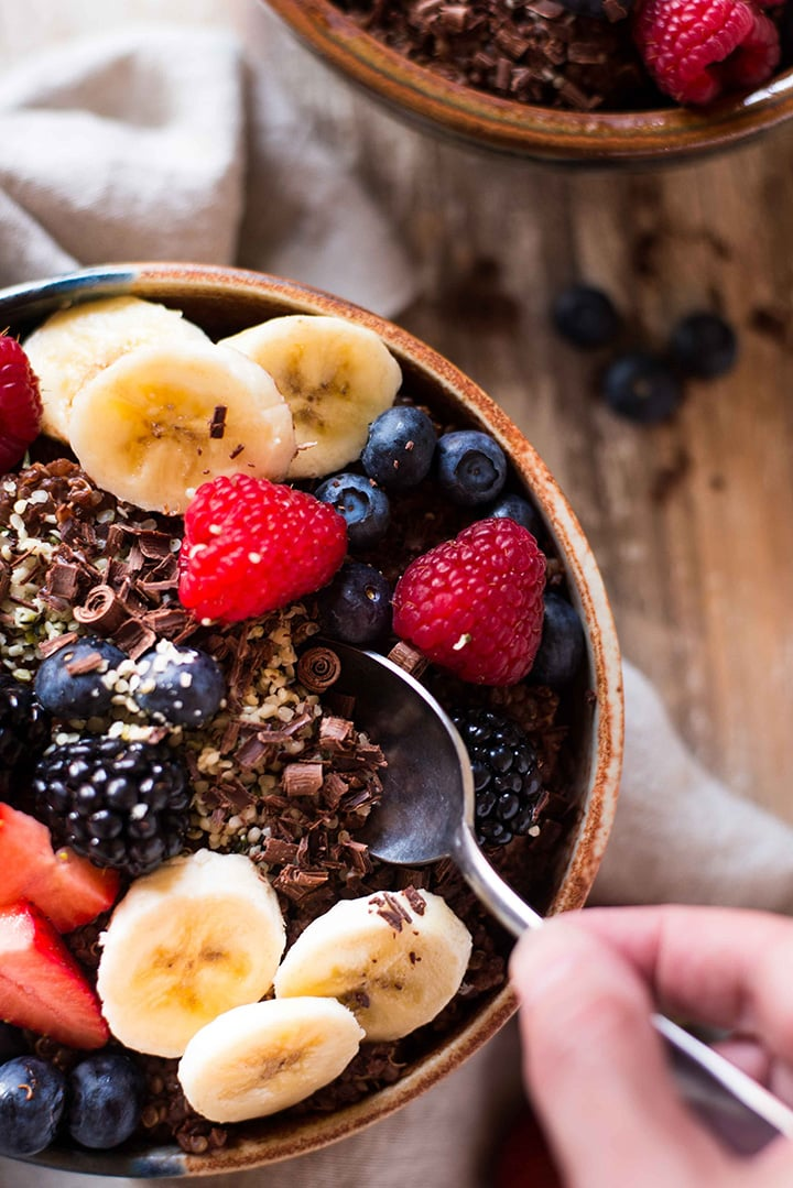 Hand with a spoon taking a spoonful of the Chocolate Quinoa Breakfast Bowl which is topped with dark chocolate shavings, bananas, and fresh berries.