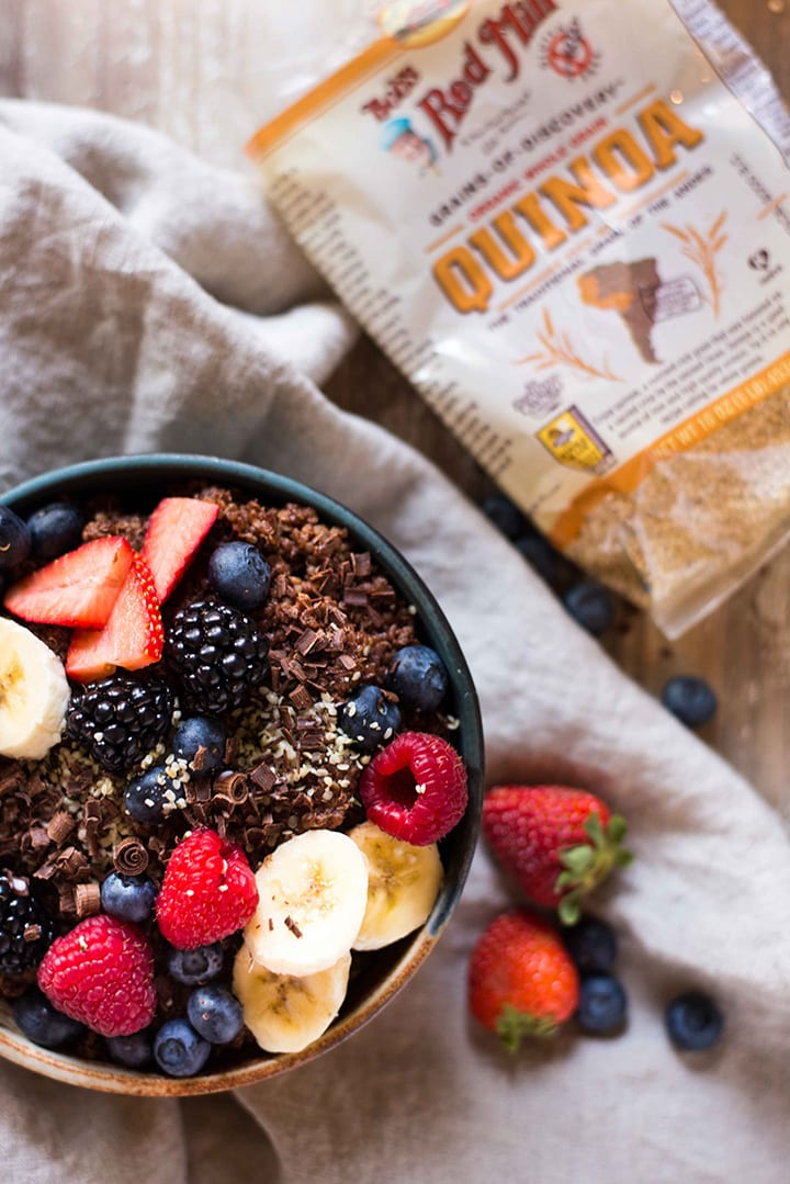 Chocolate Quinoa Breakfast Bowl which is topped with sliced bananas, fresh berries, and hempseed hearts.