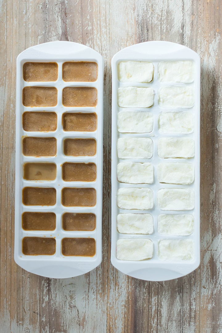 An overhead image of two ice cube trays side by side, one ice cube tray with frozen peanut butter and another ice cube tray with frozen greek yogurt ready to be added to the smoothie freezer packs.