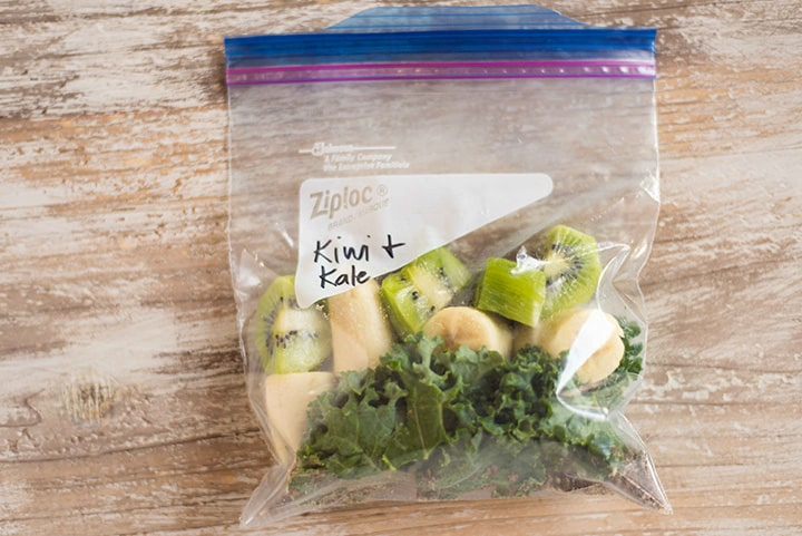 Kiwi and Kale fruit smoothie pack which contains flaxseed meal, fresh kale, banana, and fresh kiwi, tightly sealed in a 1 quart ziplock freezer safe bag.