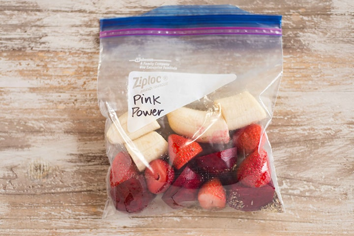 Pink Power Smoothie freezer pack that contains fresh raw beet, fresh strawberries, and banana, which is all sealed tightly in a freezer safe bag to be frozen for later.