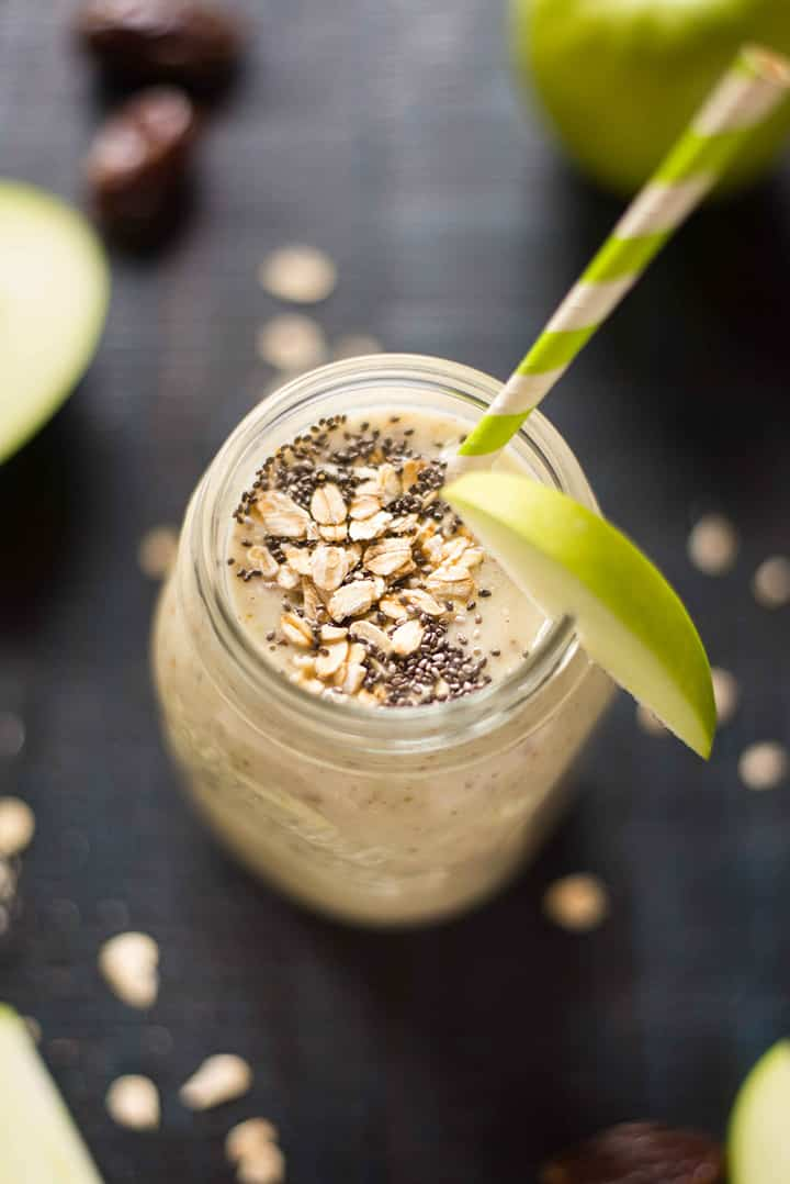 Caramel Apple smoothie w=that is topped with chia seeds, rolled oats, and fresh apple slices.