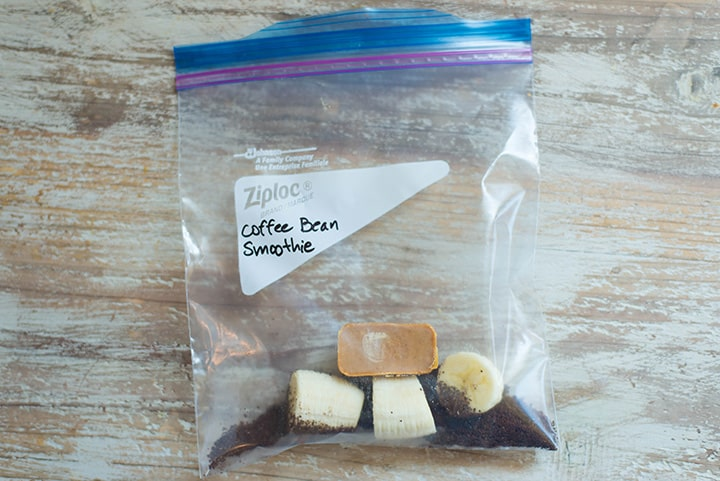 An overhead image of a smoothie freezer pack lying on the kitchen counter with the ingredients for the Coffee Bean Smoothie including banana, coffee grounds and almond butter.