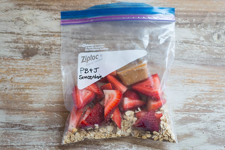 An overhead image of a smoothie freezer pack lying on the kitchen counter with the ingredients for the PB&J Smoothie including halved strawberries, oats, peanut butter and flaxseed meal.