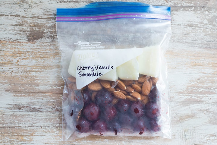 An overhead image of a smoothie freezer pack lying on the kitchen counter with the ingredients for the Cherry Vanilla Almond Smoothie including pitted cherries, whole almonds and greek yogurt.