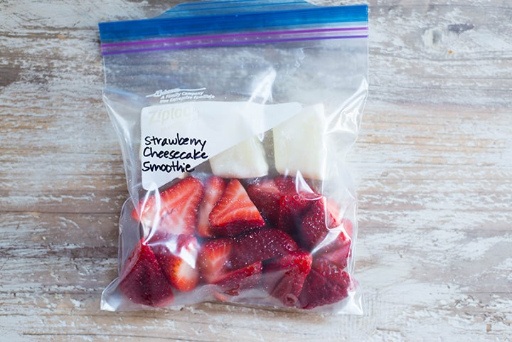 An overhead image of a smoothie freezer pack lying on the kitchen counter with the ingredients for the Strawberry Cheesecake Smoothie including halved strawberries and plain greek yogurt.