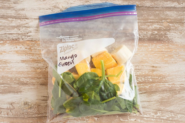 Smoothie freezer pack for mango green smoothie which contains diced frozen mango, flaxseed meal, and raw baby spinach, in a freezer-safe bag that is ready to be placed in the freezer to make the smoothie freezer pack.