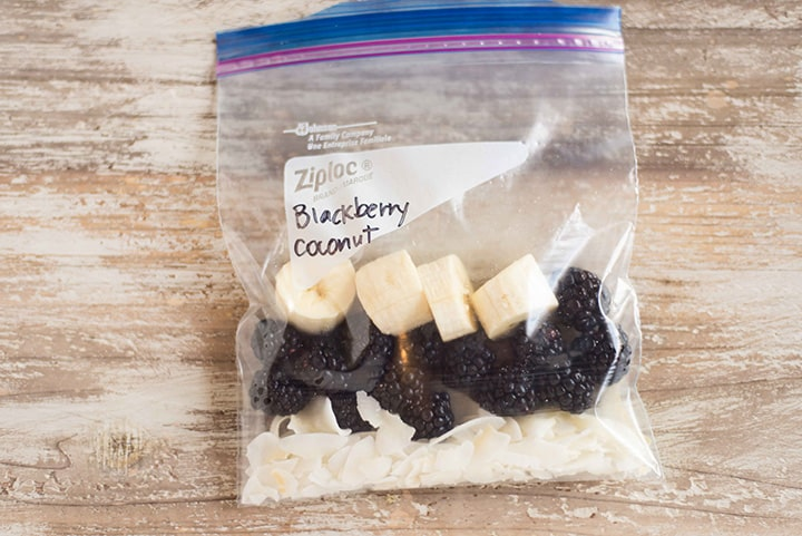 Blackberry coconut fruit smoothie freezer pack which contains raw unsweetened coconut flakes, fresh blackberries, and sliced banana, ready to be frozen in the freezer bag.
