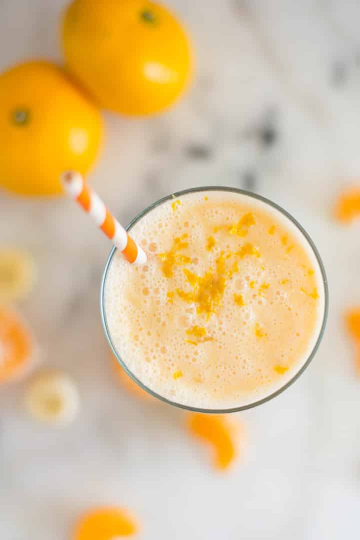 A glass of Orange Dreamsicle Smoothie with mandarin oranges, a banana, greek yogurt, vanilla extract, raw honey and almond milk topped with orange zest.