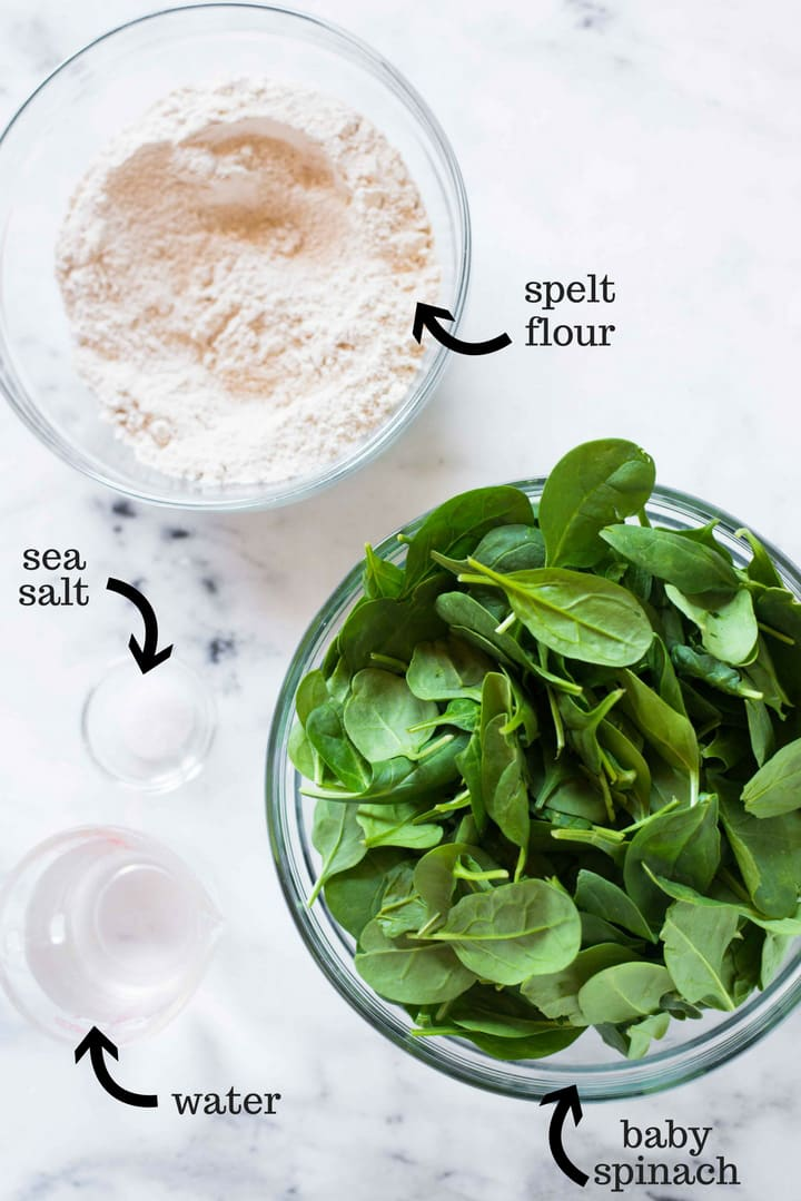 The four ingredients needed to make these homemade spinach tortillas, all separated in bowls, including baby spinach, sea salt, spelt flour, and water.