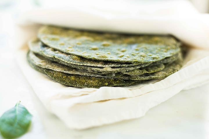 Stack of homemade spinach tortillas inside a kitchen cloth to keep them warm.