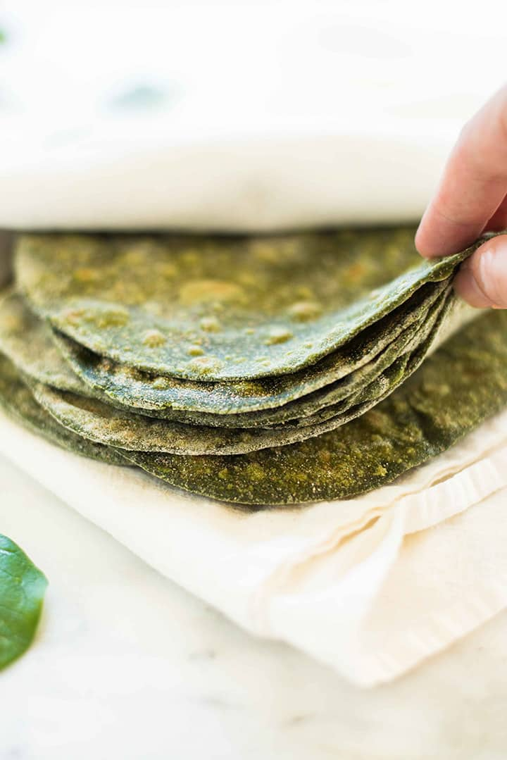 Hand flipping through the edge of a stack of homemade spinach tortillas to show how flexible they are.